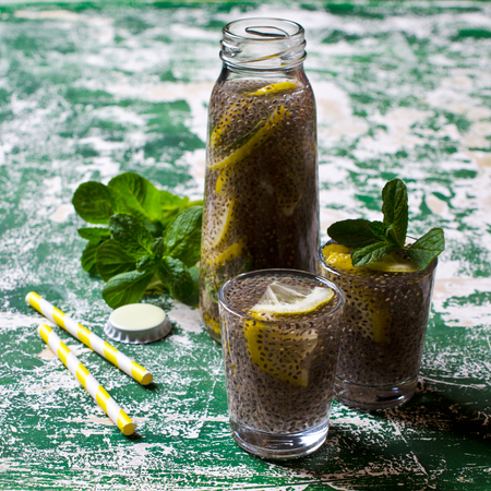 Transparent drink in a glass with chia seeds, lemon and mint on a wooden background. Selective focus. Imagens