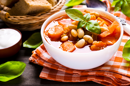 soup bowl: Thick soup with beans and vegetables on a wooden background. Selective focus. Stock Photo