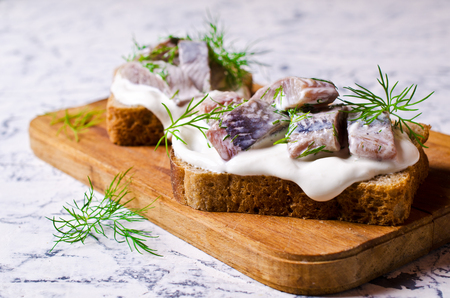 Sandwich with pieces of marinated herring with cream and dill. Selective focus. Archivio Fotografico