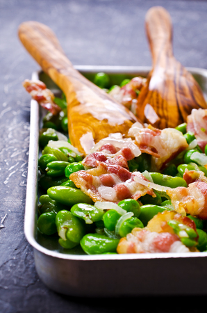 Fried bacon with broad beans and peas. Selective focus.
