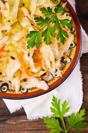 ensaladilla rusa: chucrut hecho en casa tradicional con zanahorias, semillas de hinojo y perejil fresco. enfoque selectivo.