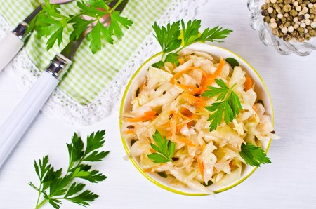 fennel seeds: Traditional homemade sauerkraut with carrots, fennel seeds and fresh parsley. Selective focus. Stock Photo