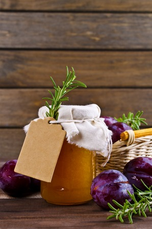 Homemade plum jam with rosemary on a wooden background. Selective focus.