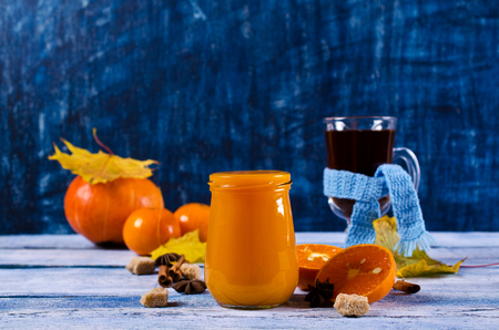 Jam from the pumpkin and citrus with spices on a wooden background. Selective focus.