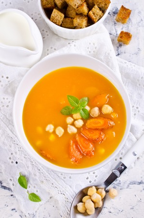 garbanzos: Pumpkin and carrot soup with chickpeas on a light background. Selective focus.
