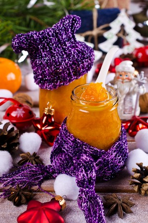 Jam of oranges on the background of Christmas entourage. Selective focus.