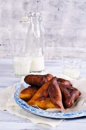 Homemade fried triangular pastry on a light background. Selective focus.