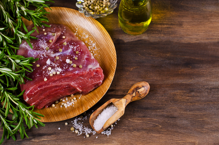 peppercorn: Raw beef fillet with spices on a wooden background. Selective focus.