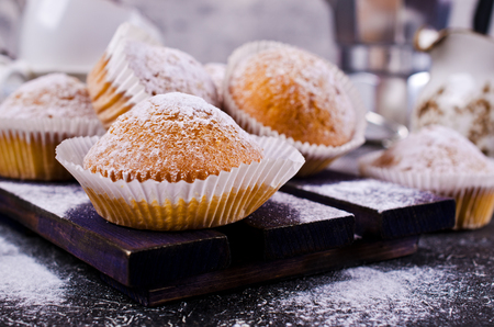 Muffins in powdered sugar on a concrete background. Selective focus.