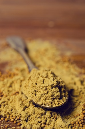 Ground mustard powder on a wooden background. Selective focus.