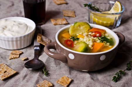Soup with vegetables and pasta on textile background. Selective focus.