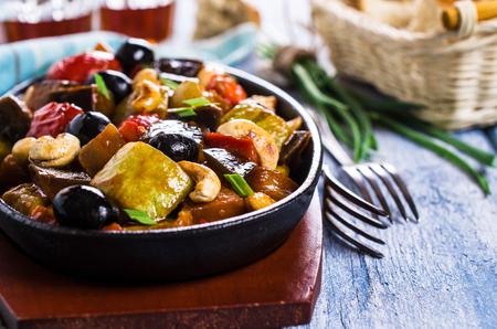 berenjena: Steamed vegetables with olives and nuts. Selective focus.