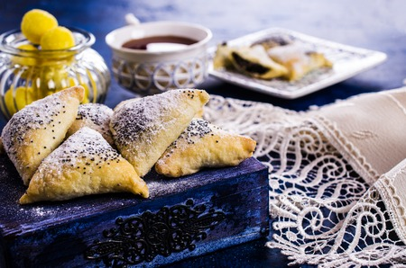 Triangular cookies with poppy seeds and powdered sugar. Selective focus. 스톡 콘텐츠
