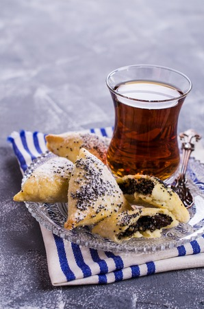hamantashen: Triangular cookies with poppy seeds and powdered sugar. Selective focus. Stock Photo