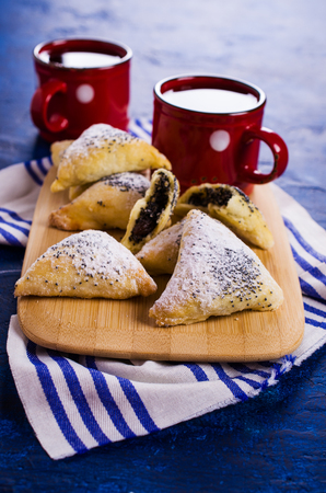 hamantash: Triangular cookies with poppy seeds and powdered sugar. Selective focus. Stock Photo