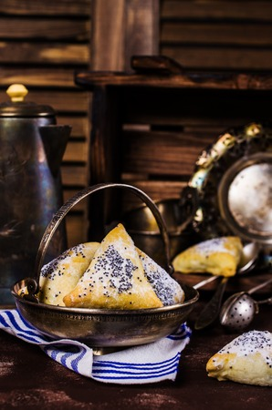 hamantaschen: Triangular cookies with poppy seeds and powdered sugar. Selective focus. Stock Photo
