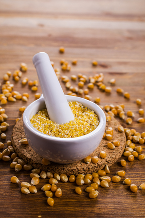 Corn grits and seeds on a wooden background. Selective focus. Stock Photo