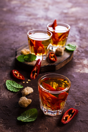 Transparent alcoholic drink with red pepper. Selective focus. Stock Photo