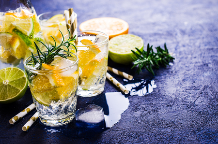 Cold lemonade with citrus and rosemary. Selective focus.