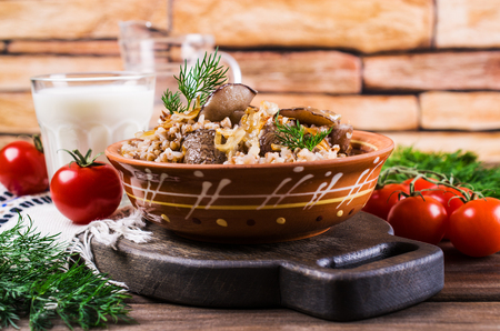 Boiled buckwheat with mushrooms and onions on a wooden background. Selective focus.