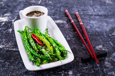 Green asparagus beans with sesame seeds. Selective focus.