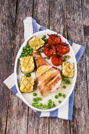 Baked fish with lemon and vegetable garnish. Selective focus.