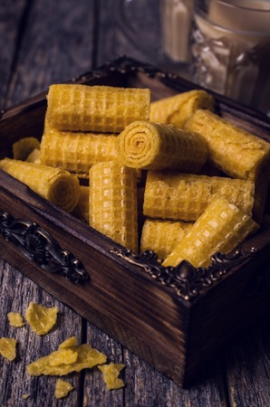 Crispy waffle rolls on a wooden background. Selective focus.