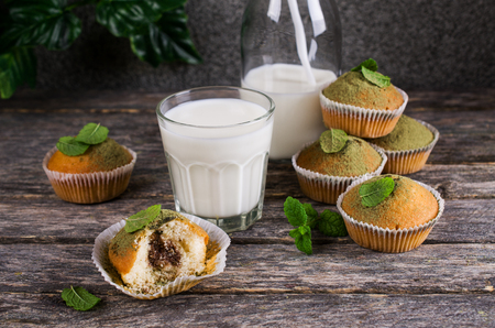 powdered: Muffins with green sugar powder and mint on a wooden background. Selective focus.