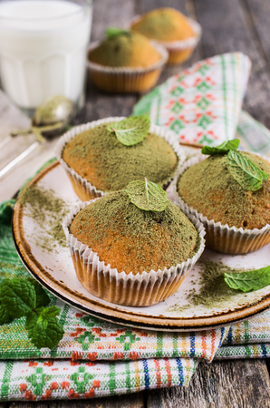 Muffins with green sugar powder and mint on a wooden background. Selective focus.