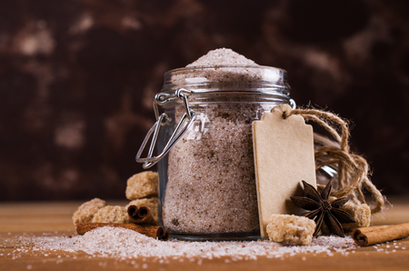 Dark sugar with cinnamon and anise on a wooden background. Selective focus.