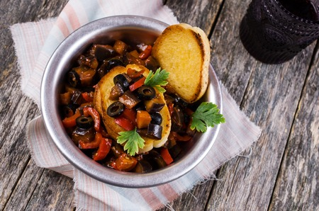 Stewed vegetables in sauce with parsley leaves and toast. Selective focus. Stock Photo