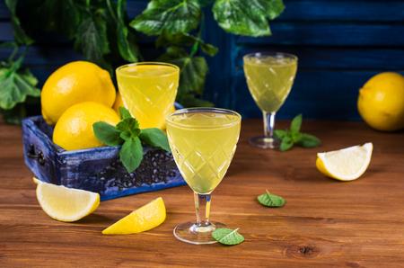 木製の背景上のレモンとイタリアの伝統的なリキュール。選択と集中。