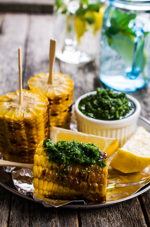 Grilled corn on sticks with green sauce. Selective focus.
