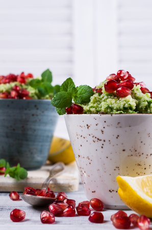 israeli: Green couscous with pomegranate and mint on a wooden background. Selective focus.
