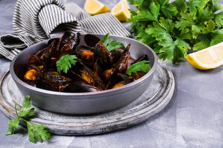 marinara sauce: Mussels in tomato sauce with parsley and lemon. Selective focus.