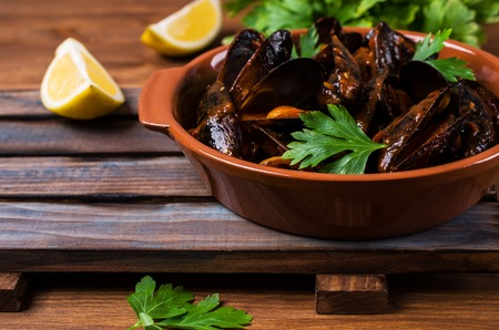 Mussels in tomato sauce with parsley and lemon. Selective focus.