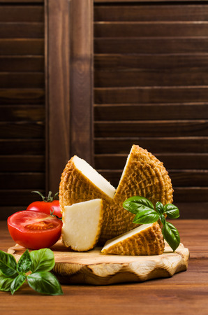 oscypek: Round smoked cheese with vegetables on a wooden background. Selective focus.