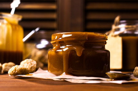 Homemade caramel sauce in the glass on a wooden background. Selective focus.