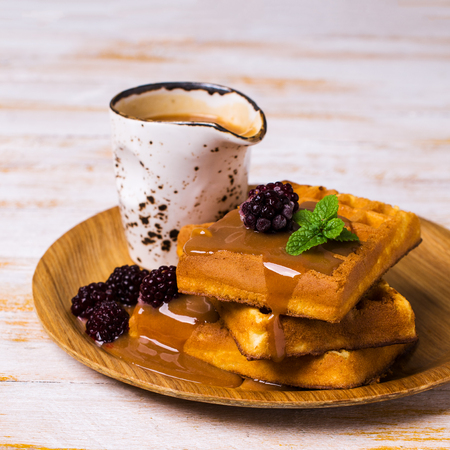 treacle: Traditional Belgian waffles with caramel topping and blackberries. Selective focus. Stock Photo