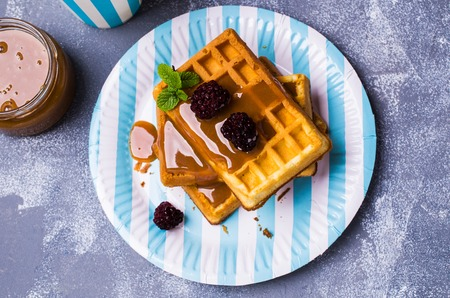 berry: Traditional Belgian waffles with caramel topping and blackberries. Selective focus. Stock Photo