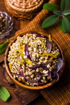 Boiled pearl barley with vegetables and herbs on a wooden background. Selective focus. Stock Photo