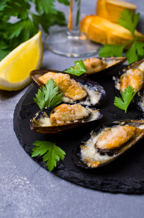 Baked mussels with cheese, parsley and lemon shells. Selective focus.
