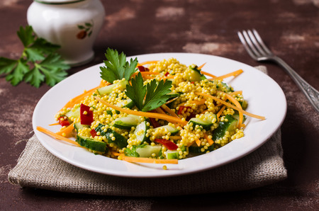 Salad with millet and vegetables in a plate. Selective focus. Imagens