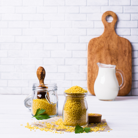 cleaned: Raw organic millet and a jug of milk on a light wooden background. Selective focus.