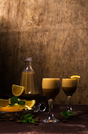Creamy coffee liqueur with caramel on a wooden background. Selective focus. Stock Photo