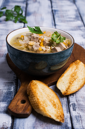 Soup with pearl barley, meat and vegetables on a wooden background. Selective focus.