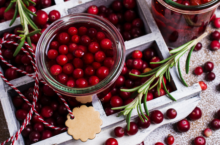 arandanos rojos: Cranberries with the syrup in glass on wooden background. Selective focus.