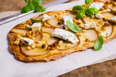Traditional pizza with pear, nuts and blue cheese on a wooden background. Selective focus. 스톡 콘텐츠