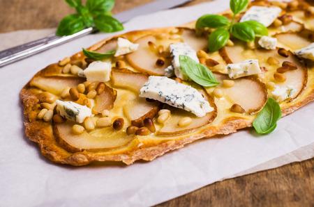 배, 견과류와 블루 치즈 나무 배경에 전통적인 피자. 선택적 포커스입니다.