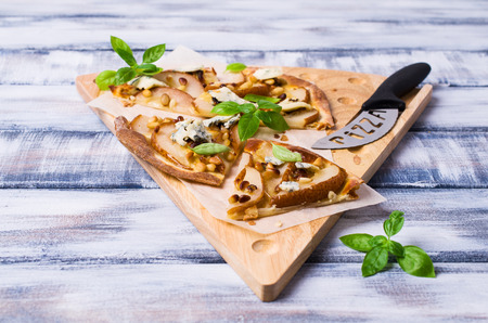 Traditional pizza with pear, nuts and blue cheese on a wooden background. Selective focus. Stock Photo